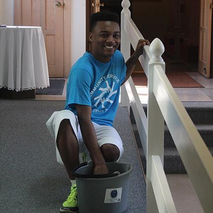 Eddie Beach (Jr) cleaning a handrail on Community Service Day 2015.