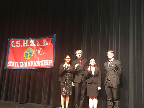Jayln Lear, Patrick Heath, Bayle Sandy and Geoffrey Pafford on stage at Valley Center High School beside the KSHSAA banner where they received their state medals Saturday night.  The team placed 10th out of 27 5A schools.